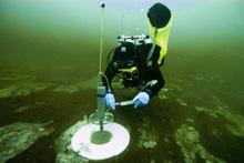 Joe Hoyt, sets up a respiration chamber experiment near the purple microbial mats