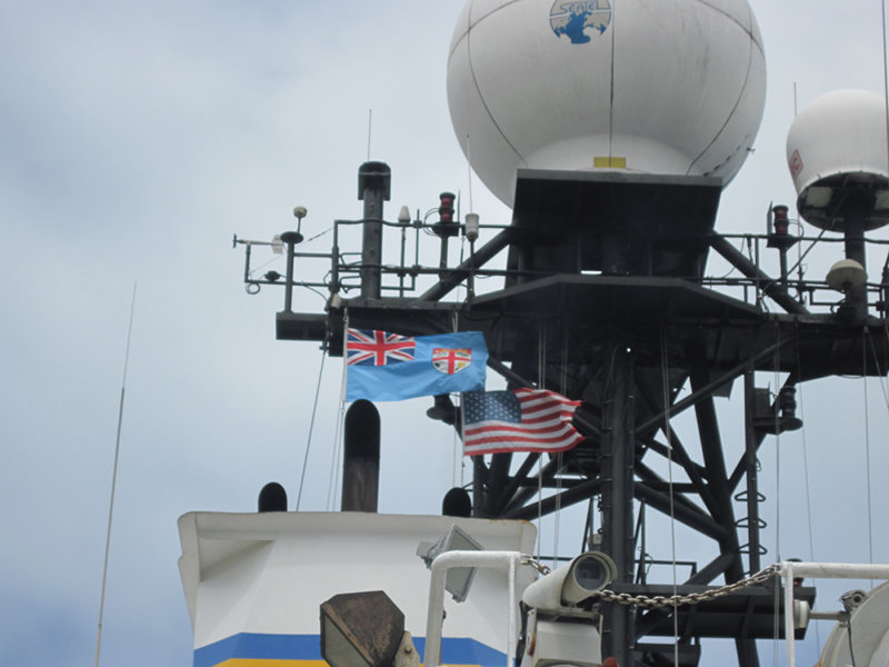 The Fijian and U.S. flags fly high atop the mast of the R/V Roger Revelle while in port in Suva, Fiji.