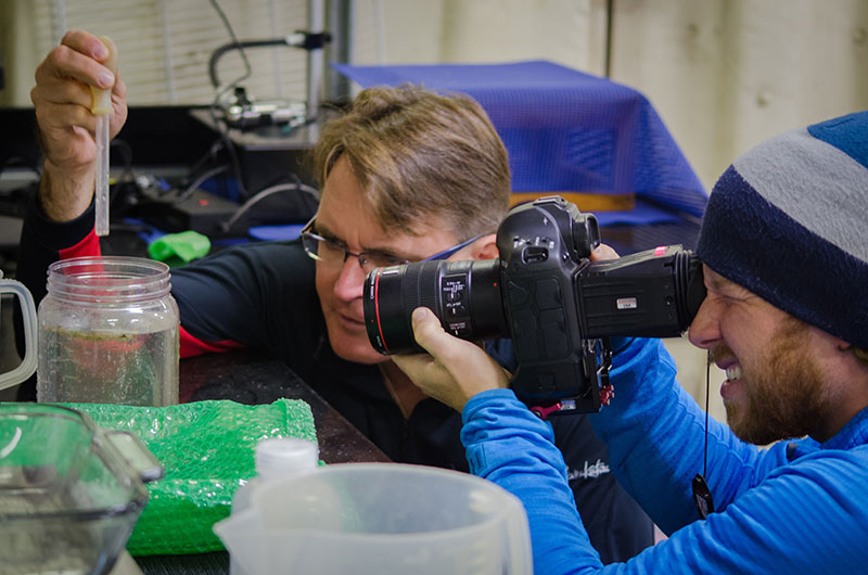 Mathew Broughton, cinematographer for Microcosm, takes footage of Dr. Dhugal Lindsay examining a jar of plankton collected from the plankton net.
