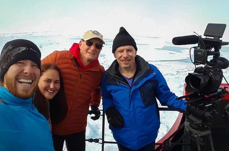 The Microcosm team (Mathew Broughton, Michele Hoffman Trotter, and Michael Caplan) take a photo with Dr. Jeff Welker after an interview on the Healy's bow.