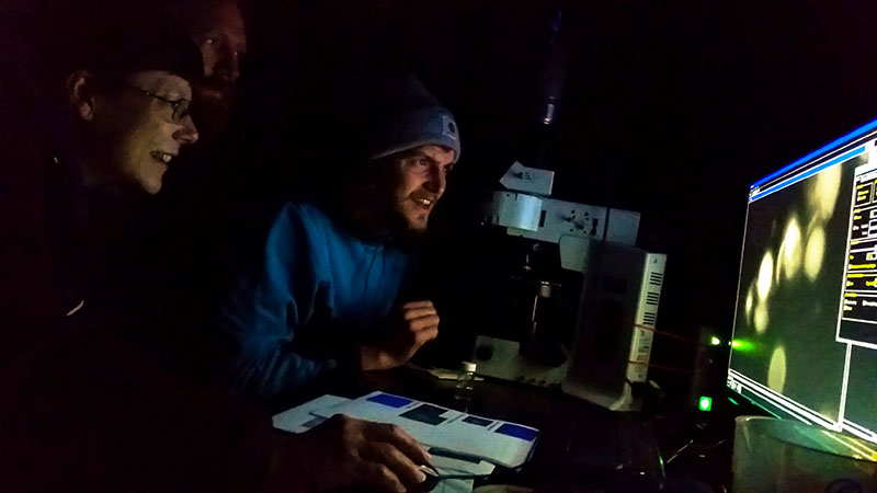 Kyle Dilliplaine and Eric Collins demonstrate their research on fluorescence and microbes to Sandra Thornton.