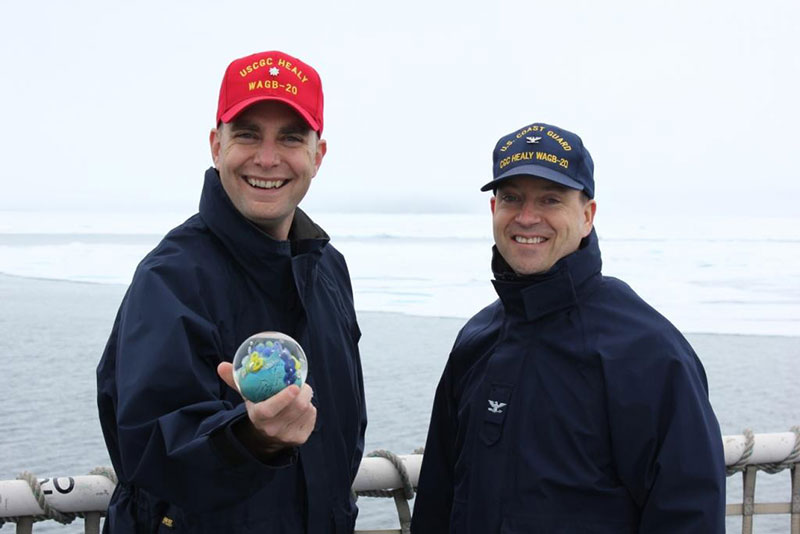 CDR William Woityra and CAPT Jason Hamilton proudly display the Planet from The Infinity Project, mentioned in the Unique Recognition for a Unique Expedition log.