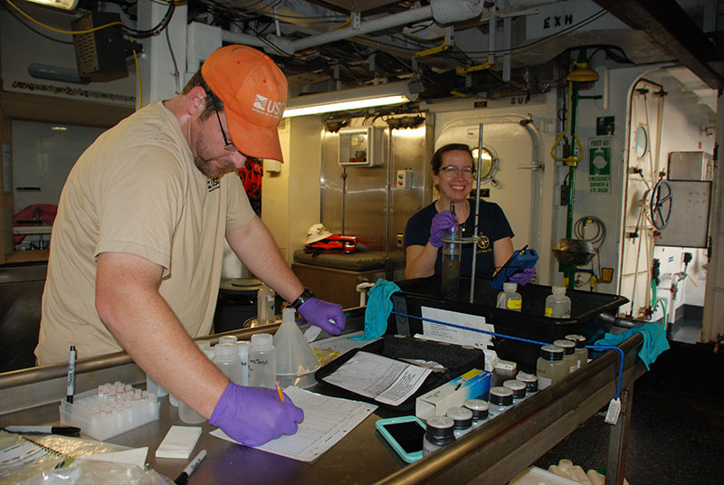 Amanda Demopoulos examines a sediment core while Jason Chaytor records her observations.