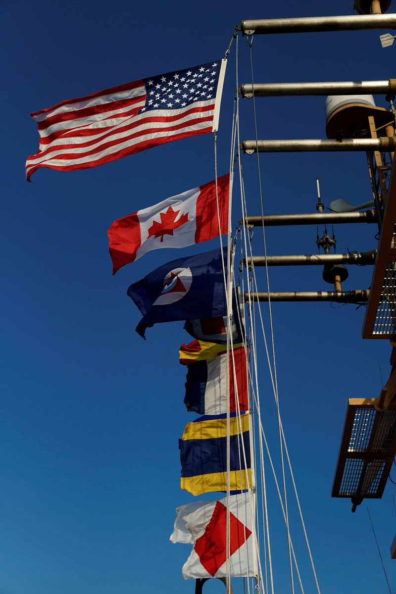All flags 'a' flying as NOAA Ship Henry B. Bigelow steams to port in Newport, Rhode Island.