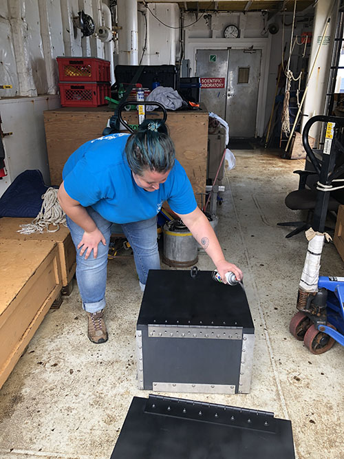 Alexis Weinnig spray paints the top of the bioboxes that will be used to safely store live coral samples collected during dives. The black matte paint helps to reduce glare that could interfere with the video cameras mounted above the sample basket.
