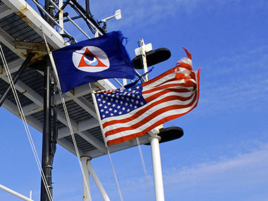 The NOAA and American flags fly above NOAA Ship Okeanos Explorer.