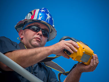Tyler Sheff, Chief Boatswain, operates ROV Deep Discoverer's crane with a wireless control.