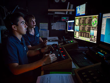 Anthony Sylvester (left) pilots ROV Deep Discoverer for the first time while Bobby Mohr watches from the navigator position.