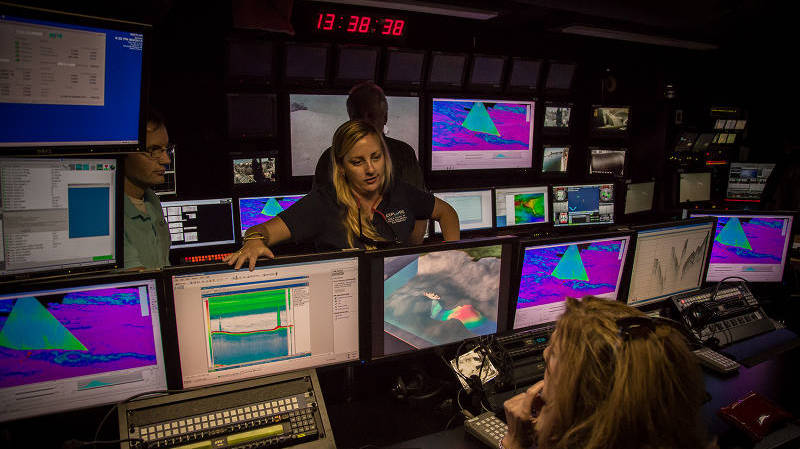 Meme explains to a group of members of the public touring the ship how Okeanos Explorer sonar systems acquire data and describes some of discoveries made using the sonar systems, including hundreds of gas seeps along the eastern seaboard.