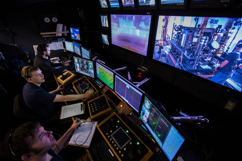 The Okeanos Explorer control room just before the start of an ROV dive. The control room is where the ROV pilots, the science leads, and other expedition personnel work during an ROV dive.
