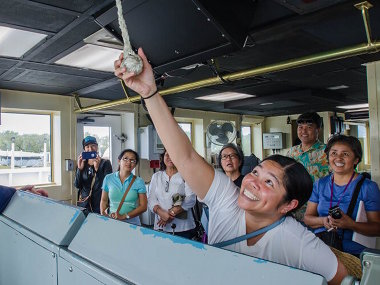 "A teacher participant in the ""Why Do We Explore"" workshop pulls the foghorn of NOAA Ship Okeanos Explorer while visiting the bridge during a tour of the ship."