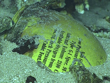 This yellow tank is an oxygen cylinder used in the system to pressurize the crew's cabin spaces. It is in remarkably good condition with the writing still legible.