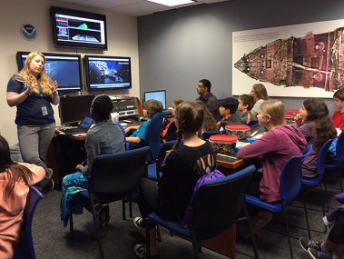 OER's Kasey Cantwell addresses a group of students at an Exploration Command Center.