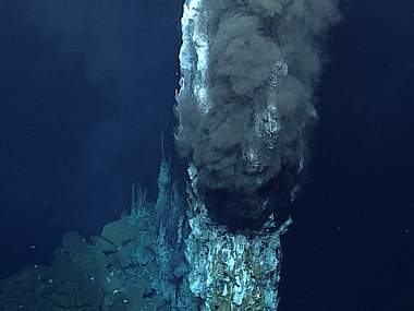 "A ""black smoker"" on Dive 11. Where the super-hot vent fluid meets very cold ambient sea water (2°C) of the deep sea, minerals that are carried in the fluid precipitate out of solution, forming spectacular vent chimneys. We measured the temperature of the vent fluid at 339°C."
