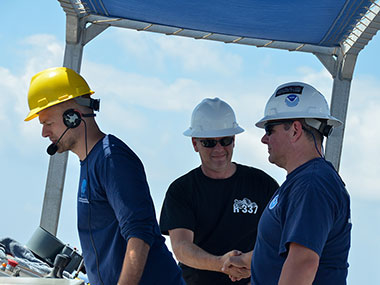 NOAA Ship Okeanos Explorer Operations Officer, LT Aaron Colohon, shakes Commanding Officer, CDR Eric Johnson's hand following successful recovery of the remotely operated vehicle (ROV).