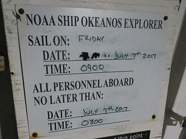 Picture of the sailing board on NOAA Ship Okeanos Explorer showing the date and time of departure for the next cruise and the time by which all personnel who are sailing need to be physically on board the ship to sail.