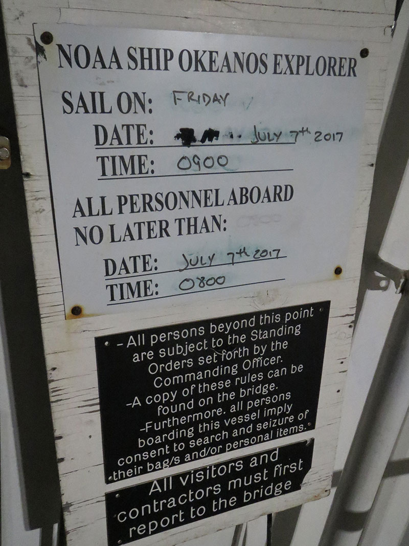 Picture of the sailing board on NOAA Ship Okeanos Explorer showing the date and time of departure for the next cruise and the time by which all personnel who are sailing need to be physically on board the ship to sail. Cruise EX-17-06 departed on time at 0900 on Friday, July 7, as planned.