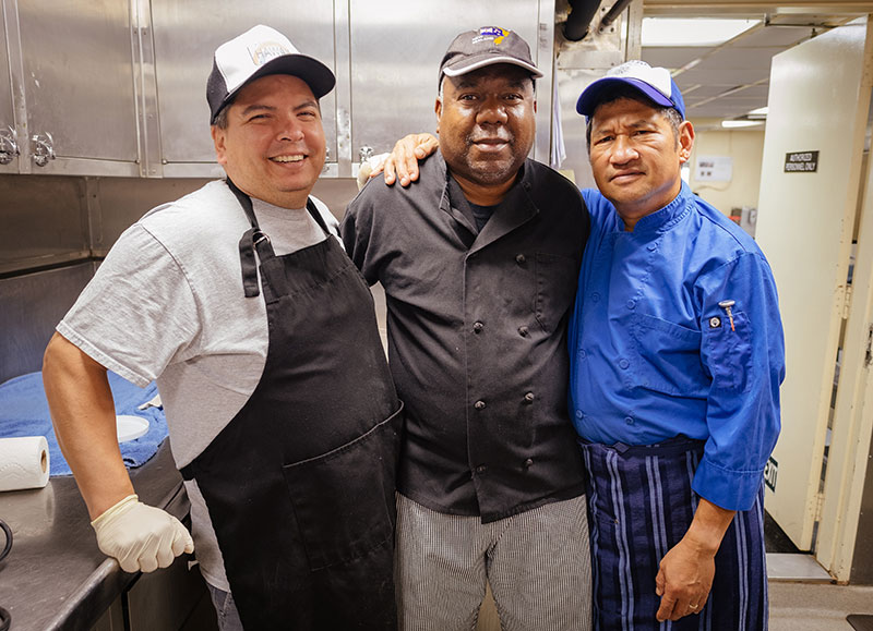 Chief Steward, Mike Sapien; Second Cook, Will Johnson; and Chief Cook, Ray Capati in the galley aboard NOAA Ship Okeanos Explorer.