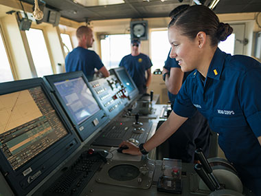 ENS Brianna Pacheco using the ship's Electronic Chart Display Information System (ECDIS) to navigate the ship.
