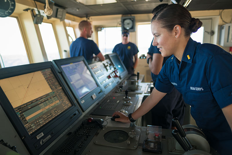 "ENS Brianna Pacheco using the ship's Electronic Chart Display Information System (ECDIS) to navigate the ship. ECDIS is an ""industrial-sized"" navigation app that encompasses electronic navigation charts, GPS, gyrocompass, radar, depth sounder, autopilot, automatic route safety scanning programs and a host of other electronic tools."