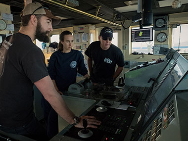 Kongsberg DP Technician, Michael Neal, provides training on use of the ship's Dynamic Positioning system to NOAA Corps Officers ENS Anna Hallingstad and LT Aaron Colohon.