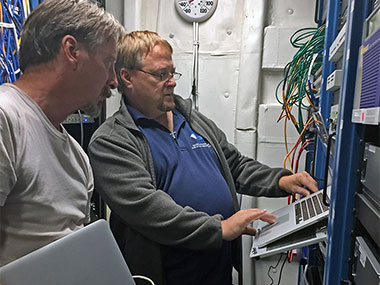 Telepresence Engineer, Roland Brian, and Senior Electrical Engineer, Dave Wright, verifying configuration of the telepresence network switch in the ship's rack room.
