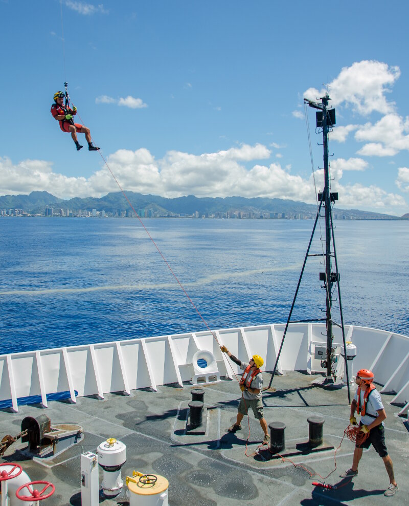 A U.S. Coast Guard rescue swimmer is deployed to the bow of NOAA Ship Okeanos Explorer during a training drill off the coast of Oahu, Hawaii.