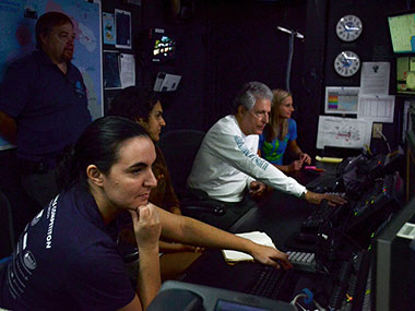 Alex and other members of the on-ship team receive training from Global Foundation for Ocean Exploration engineer Roland Brian in the Okeanos Explorer's control room.