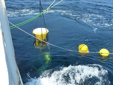 U.S. Geological Survey sediment trap and streaming floats being deployed off the stern of NOAA Ship Nancy Foster.