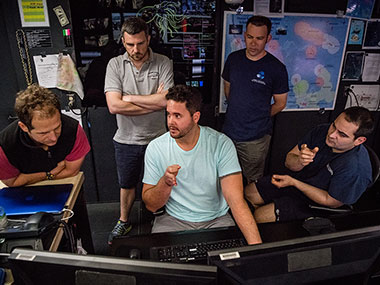 Lead Scientists, Daniel Wagner and Adam Skarke (from the left), discuss mapping with NOAA Ship Okeanos Explorer Mapping Lead, Mike White (center), Global Foundation for Ocean Exploration ROV Team Lead Karl McKletchie (second from right), and Expedition Coordinator, LT Nick Pawlenko (far right).