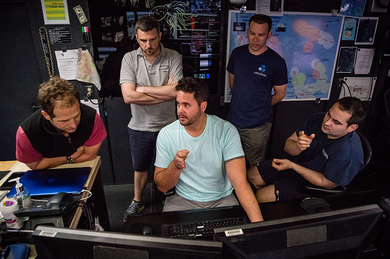 Lead Scientists, Daniel Wagner and Adam Skarke (from the left), discuss mapping with NOAA Ship Okeanos Explorer Mapping Lead, Mike White (center), Global Foundation for Ocean Exploration ROV Team Lead Karl McKletchie (second from right), and Expedition Coordinator, LT Nick Pawlenko (far right) during the Gulf of Mexico 2018 cruise.
