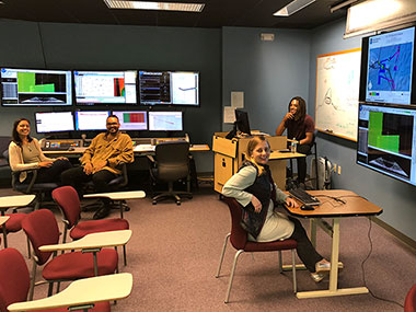Image of NOAA Ship <em>Okeanos Explorer</em> onshore mapping team at the University of New Hampshire Exploration Command Center participating through telepresence.
