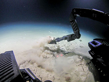 Remotely operated vehicle (ROV) Deep Discoverer collects a geological sample of the seafloor sediment using the scoop tool.