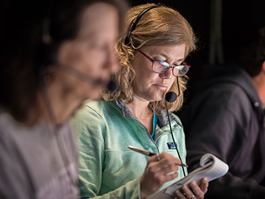 Expedition co-science lead and biologist, Cheryl Morrison, in the control room on NOAA Ship Okeanos Explorer taking notes of the species seen during a dive for the Windows to the Deep 2018 expedition.