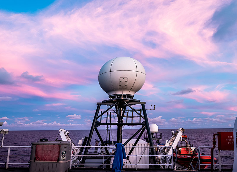 The sun sets over the VSAT or Very Small Aperture Terminal antenna that allows for real-time sharing of our exploration data and live video through telepresence.