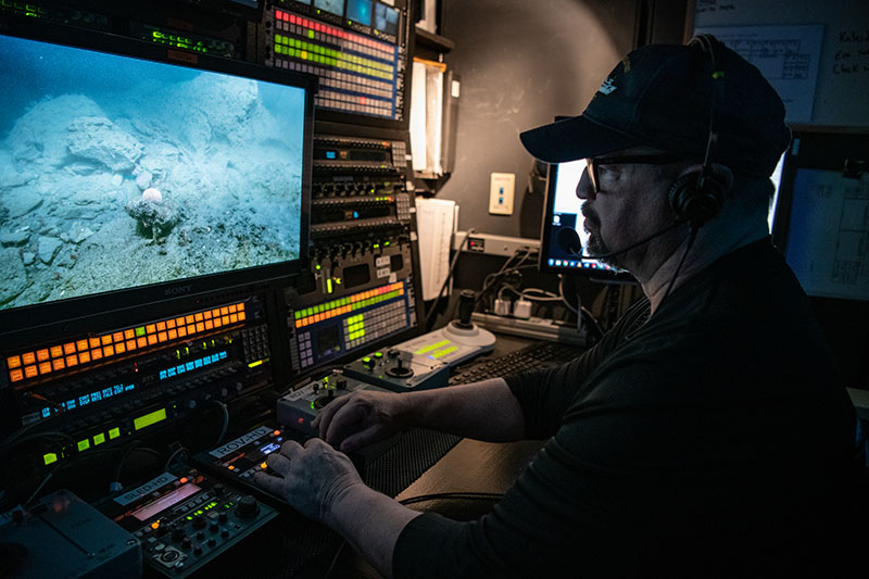 Video Engineer Brian Doros controlling video shading during a ROV dive of the Deep Connections 2019 expedition. Video shading refers to the task of controlling the ROV cameras to ensure that images are well lit and in focus.